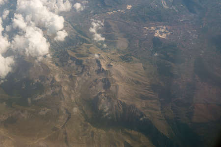 Aerial view mountains, little city and stone quarrys as seen from airplane, drone Foto de archivo