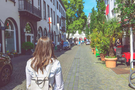 Traveler girl in shirt with backpack walk by old town street. concept of student travel, summer vacation, solo female tourism, adventure. palma de mallorca old town. Foto de archivo