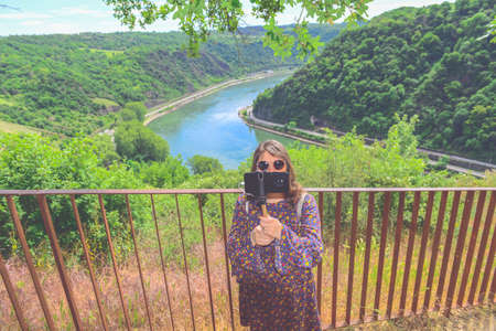 Summer sunny lifestyle fashion portrait of young stylish hipster woman walking in mountains, wearing cute trendy outfit, smiling enjoy weekends, travel with backpack. awesome water, river view on a background Foto de archivo