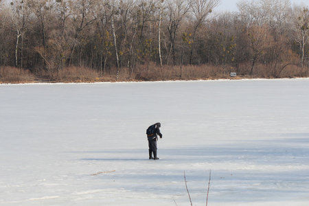 fisherman measures the thickness of the ice