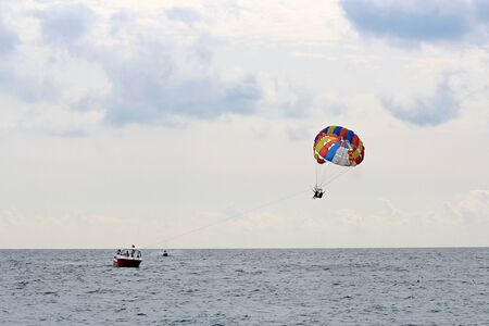 parachute flying over the Mediterranean Sea against a cloudy sky