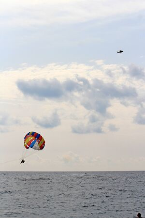 parachute flying over the Mediterranean Sea against a cloudy sky Фото со стока - 132220928