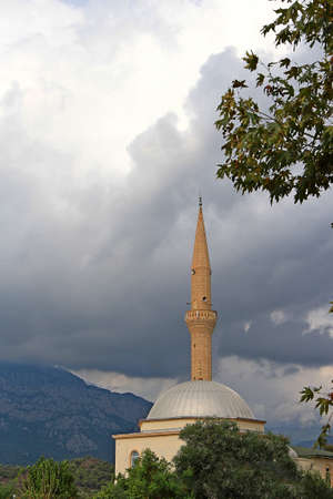 mosque with mountains and storm clouds in the background