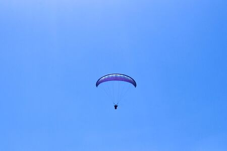 paraglider flying in blue sky on valleys landscape in Indonesia 版權商用圖片