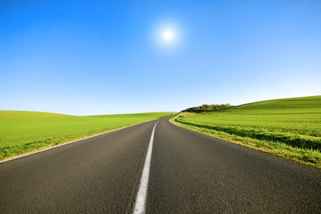 ahead: An empty road with a white line down the middle. Stock Photo