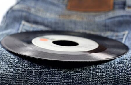 a vinyl record on a pair of jeans