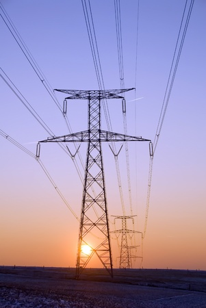 ligne: sunset behind high voltage pylons Stock Photo