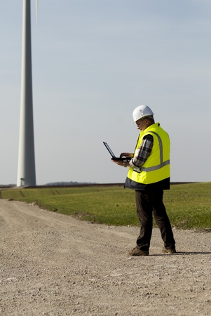 windturbine:  technician is tapping on his laptop with a windturbine in the background