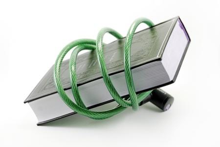 illiteracy: un libro rodeado de un candado de cable Foto de archivo