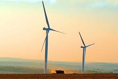een maaidorser tussen twee windturbines