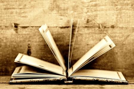 een open boek in sepia kleuren en houten achtergrond