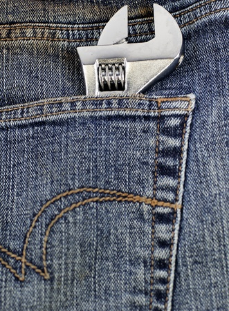 an adjustable wrench in a jeans pocket photo