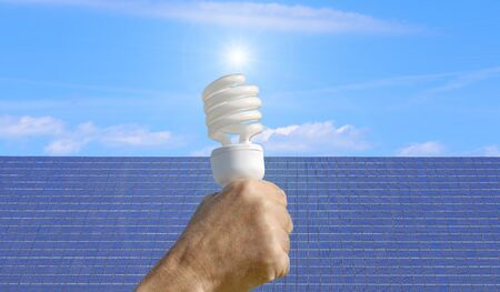 solarpanel: energy saving bulb and solar panel in the background