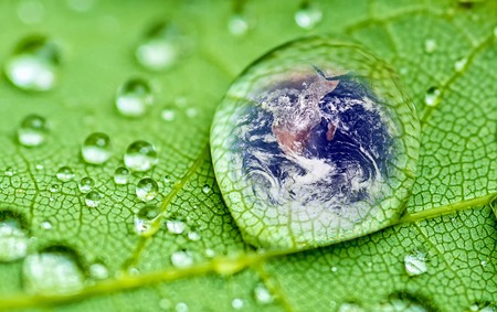 ecology  environment: planet earth inside a raindrop closeup on a green leaf (Elements of this image furnished by NASA ) Stock Photo