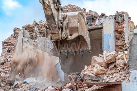 house demolition: excavator at work on a house demolition site Stock Photo
