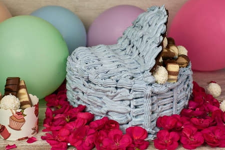 homemade heart shaped like a box blue-violet cake with chocolate pralines and coconut, decorated with pink flowers and colorful balloons
