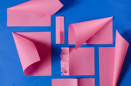 Pink paper cutouts on an isolated blue background, three-dimensional effect on striking colors.