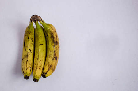 Group of three ripe bananas, on an isolated white background, shot taken from above. 免版税图像