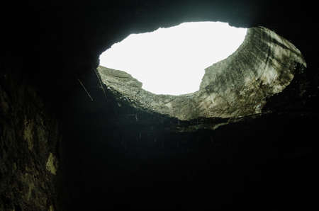 a hole on the roof of an old structure, raindrops falling on the hole in an abandoned roof.