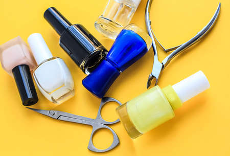 Set for nail care, manicure tools scissors, nippers, varnish on a yellow background