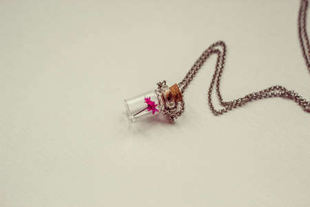 small pink flower in a glass flask, vintage decoration