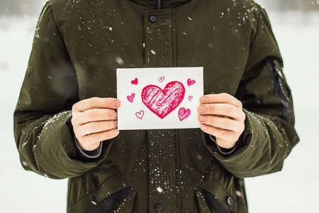 Man holding white card with love