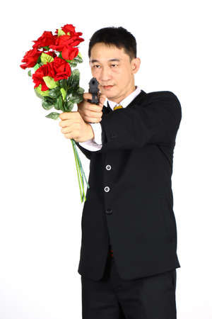 risky love: Asian business community Holding a bouquet of roses and a gun. Treacherousness Stock Photo