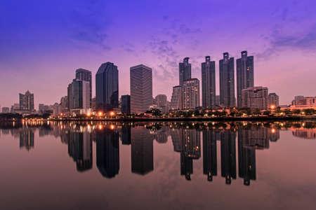 urbanscape: Cityscape of Benjakitti park Bangkok city downtown at sunrise with reflection, Bangkok Thailand. Stock Photo