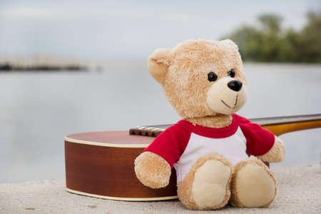 osos de peluche: Ukulele and teddy bears on  river side in the evening. Foto de archivo