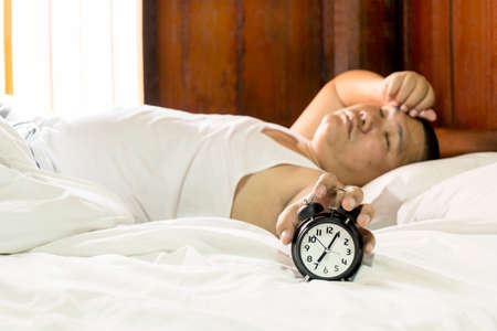 sleeplessness: Monday morning Asian man lying on the bed. Lazy Man concept Stock Photo