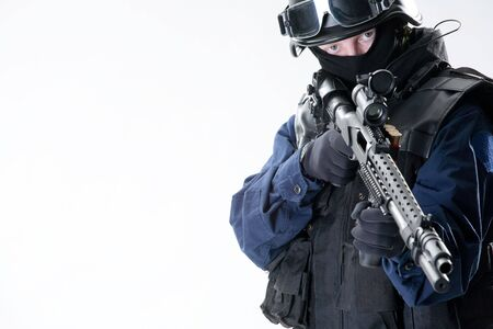 The soldier in the black form costs with a gun Stock Photo