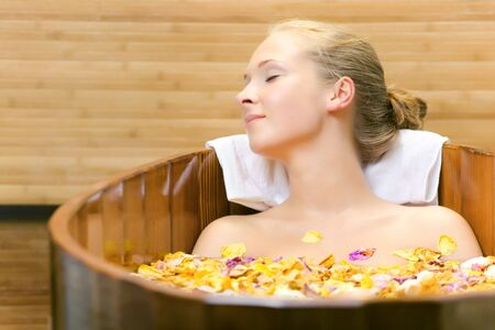 EASE: The young woman has a session spa in a wooden bath Stock Photo