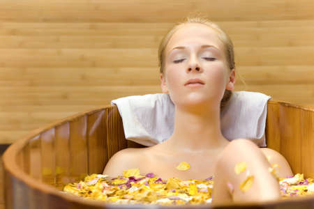 wife of bath: The young woman has a session spa in a wooden bath Stock Photo