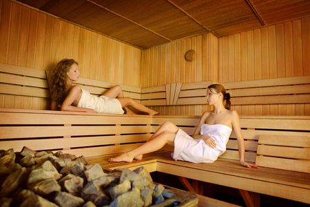 Two beautiful women have a sauna session Stock Photo