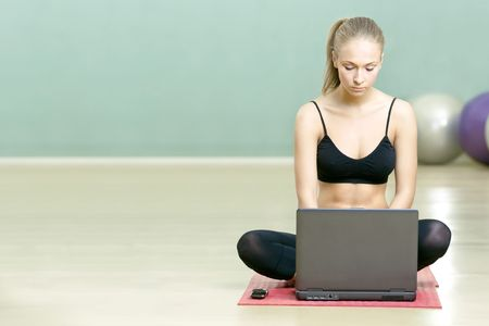 The beautiful girl sits with the laptop in sports hall photo