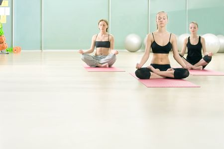 lotos: Three young girls meditate in sports gym