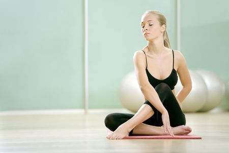 The young girl meditates in sports to a gym Stock Photo - 4903593