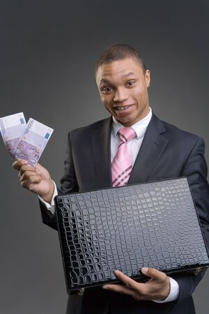 The businessman gets money from a briefcase photo