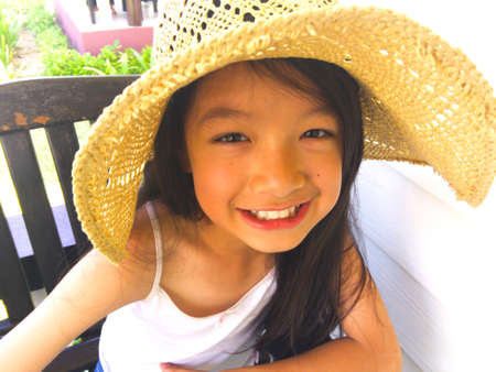 Asian long black hair girl is smiling who revealing white teeth and sitting on the wooden chair. She is wearing straw light brown hat and white vest.