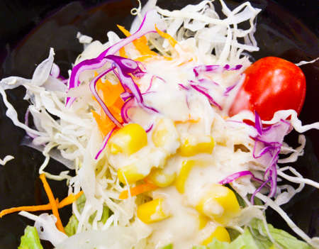 Vegetable salad in black bowl, consist of boiled corn, tomato, cabbages, purple cabbage, carrots and raddish, which was topped with mayonnaise.