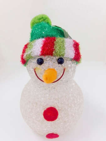 Snowman wearing a green hat, isolated on white background with clipping path. Stock Photo