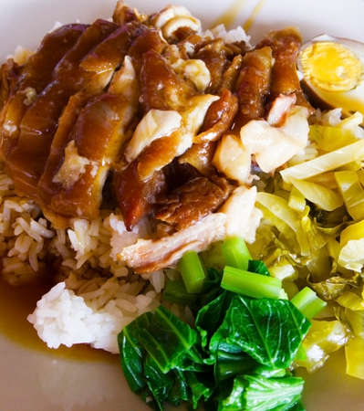 Stewed pork leg on rice with side dishes are boiled egg, pickled vegetable and soft-boiled kale, that are on the white plate.