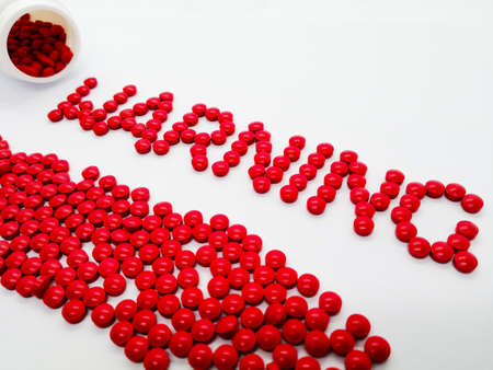 Word warning made from red tablets, isolated on white background. the concept of drug use warning, side effect, drug overdose and drug use than necessary. Stok Fotoğraf