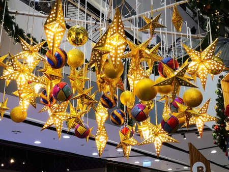 Many beautiful golden stars with light bulb inside and many colorful ball, which are hanging down from the ceiling. Concept for decoration.