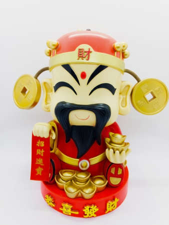 God of prosperity doll or Deity figurine holding a message 'Prosperity' and 'Money and Fortunes Come'. Concept of Chinese Lunar New Year. Isolated on white background with clipping path.