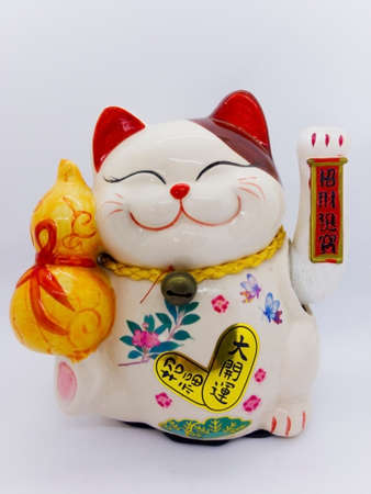 Maneki-neko is name of lucky cat, Symbolizing lucky and wealthy. Isolated on a white background with clipping path.