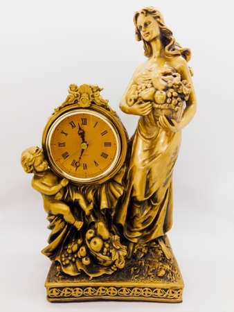 Bronze desk clock, woman holding a fruit basket and  little boy sitting next to clock. Isolated on white background with clipping path.