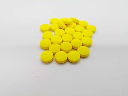 Medication and healthcare concept. Many yellow pills of Metronidazole 200 mg. isolated on white background, used to treat bacterial infections. Focus on foreground and copy space.