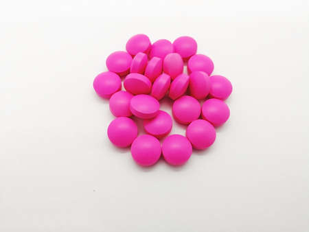 Medical and healthcare concept. Many round pink tablets of Erythromycin 250 mg. isolated on white background, used to treat or prevent many different types of infections. Selective focus and copy space. Stock Photo