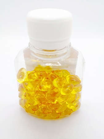 Medication and healthcare concept. Many yellow capsules of Cod liver oil 275 mg.  Focus on foreground and copy space.